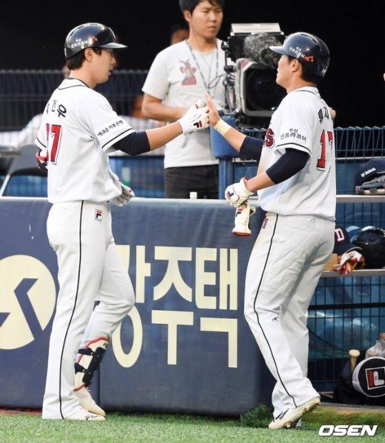 선제 결승 희생플라이를 친 박건우(좌)와 득점한 류지혁이 하이파이브를 나누는 모습.