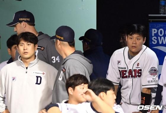 김태형 두산 감독(오른쪽에서 두 번째 뒷모습)이 퇴장 판정을 받자 더그아웃을 빠져나가고 있다. 이를 지켜보고 있는 두산 선수단.