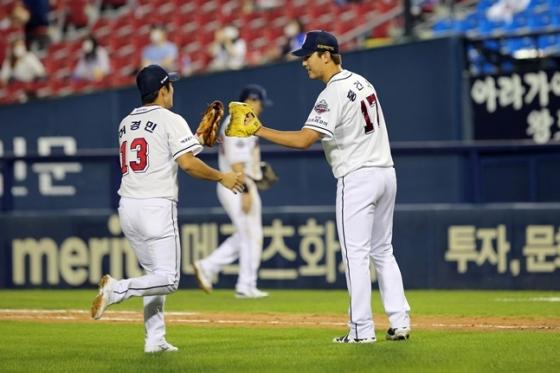 허경민과 글러브 하이파이브를 나누고 있는 홍건희(오른쪽). /사진=두산 베어스 제공