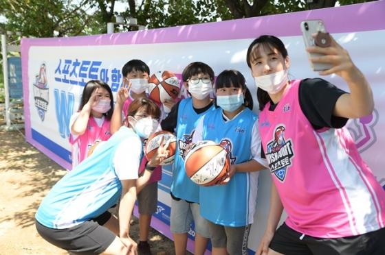 13일 희망터지역아동센터 코트 기증식에서 아이들과 사진을 찍고 있는 김단비(오른쪽)와 이경은(아래 왼쪽). /사진=WKBL 제공