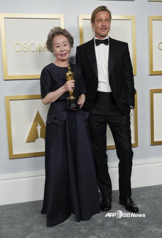 윤여정이 한국배우 최초로 아카데미 시상식에서 여우조연상을 수상한 뒤 '미나리' 제작자로 이름을 올린 브래드 피트와 포즈를 취하고 있다. /AFPBBNews=뉴스1