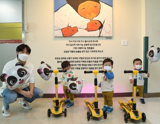 이른둥이로 태어났던 이승훈군이 이른둥이 세 쌍둥이에게 사랑의 킥보드 선물을 전달하고 있다/사진제공=이대목동병원