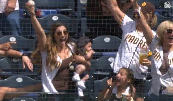 한 여성 관중(왼쪽)이 왼팔에 아기를 안은 채 파울볼을 잡고 기뻐하고 있다. /사진=MLB.com 영상 캡처