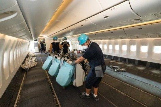 대한항공 직원들이 화물 운송을 위해 여객기에서 좌석을 제거하고 있다