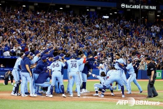 토론토 선수들과 팬들이 지난 4일(한국시간) 캐나다 토론토 로저스센터에서 끝내기 홈런을 친 마커스 세미언을 환영해주고 있다./AFPBBNews=뉴스1