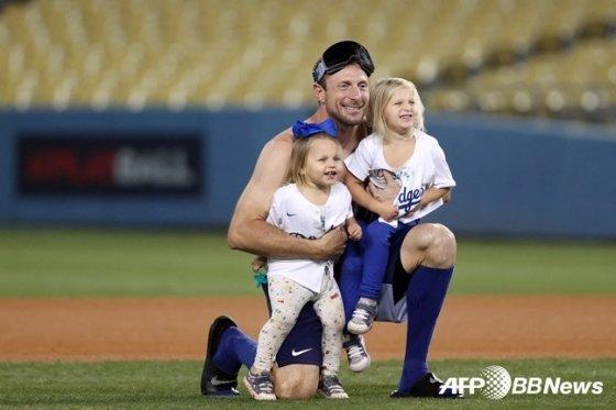 LA 다저스 투수 맥스 슈어저(가운데)가 지난 7일(한국시간) 세인트루이스와 와일드카드 경기에서 승리한 후 두 딸과 함께 기념 촬영을 하고 있다.  /AFPBBNews=뉴스1